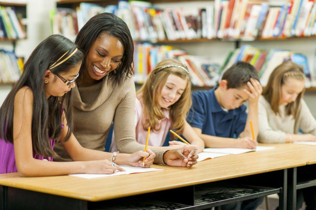 Teacher helping students in classroom - TeacherMade